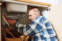 Klempner repariert defekten Abfluss der Küchenspüle