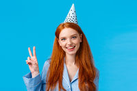 Lucky and enthusiastic feminine pretty redhead woman with long curly hair in nightwear, wearing birthday cap showing peace sign and smiling joyfully, celebrating b-day, blue background