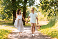 happy couple with picnic basket at summer park