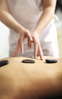 Woman during hot stone massage in spa salon