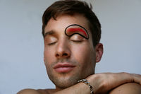 Portrait of young caucasian man with creative make-up on his face. Isolated.