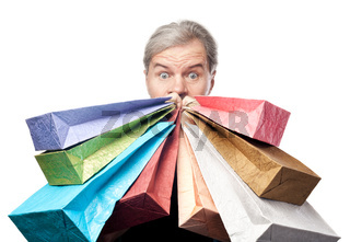 surprised mature man holding shopping bags near face isolated on white background