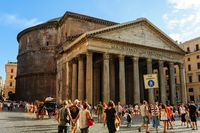 Ancient pantheon exterior daytime with crowded square in Rome, Italy