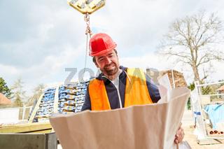 Architekt oder Vorarbeiter mit Bauplan auf der Baustelle