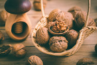 Organic walnuts with small nutcraker as baking ingredients on wooden background