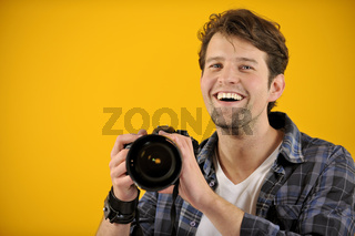 Fotograf mit Spiegelreflexkamera vor gelbem Hintergrund