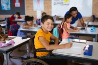 Portrait of disabled caucasian boy smiling while sitting on wheelchair in class at elementary school