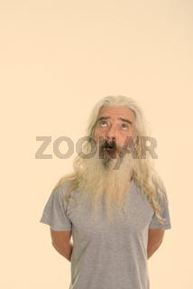 Studio shot of senior bearded man thinking while looking up with hands on back