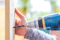 Do it yourself: Home Handyman is using a drilling machine for drilling wood