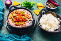 Hot Mexican Chili con carne with rice and tortilla chips and spices
