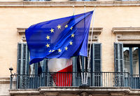 The flag of the European Community flying above the Italian flag on the balcony of a public building