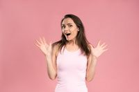 Surprised pretty young woman wearing pink t-shirt with hands in the air, excited and joy expression on her face with positive emotions. Facial expressions, emotions, feelings