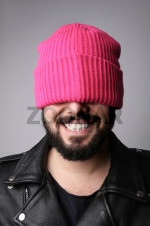 Vertical portrait of young happy handsome bearded man, wearing pink hat.