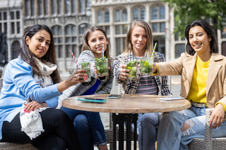 May 21, 2021, Antwerp, Belgium, Four attractive young woman of mixed race toasting with a cocktail outdoor in the city center after the reopening of bars closed for corona or covid-19 restrictions