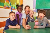 Kinder und Kindergärtnerin strecken die Zunge heraus