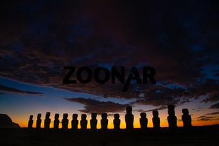 Dramatic colorful sunrise over Moai stone sculptures at Ahu Tongariki, Easter island, Chile.