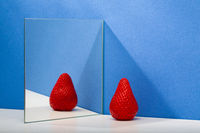 A fresh and tasty strawberry reflected in the mirror on the blue background.