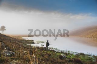 Sport fisherman fishing in lake on cloudy day.