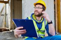 Architekt auf Baustelle mit Checkliste und Smartphone