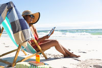 Mixed race smiling woman on beach holiday sitting in deckchair using tablet