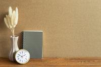 Notebook, clock, dry flower on wooden desk. brown wall background. Workspace