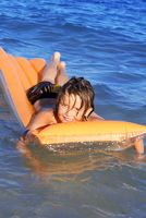 young kid floating in sea playing on airbed or lil