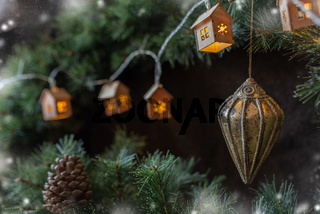 Christmas tree garland in the form of small Scandinavian houses cozy on a fir tree branch.