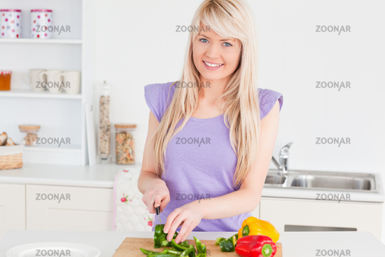 Beautiful blonde woman cutting vegetables in modern kitchen interior
