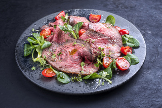 Modern style traditional Commonwealth Sunday roast with sliced cold cuts roast beef served with tomatoes and corn lettuce as close-up on a Nordic design plate with copy space