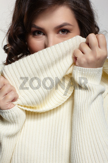 Brunette beautiful woman dressed in large white woolen sweater on gray background.
