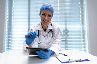 Caucasian female doctor at desk using tablet and smiling during video call consultation