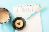 To do list. A paper notebook with a blue pen and a coffee mug, overhead flat lay