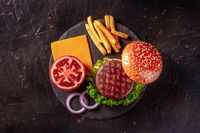 Burger ingredients, shot from the top on a black slate background