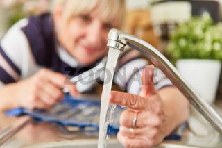 Frau als Heimwerker prüft Temperatur vom Warmwasser