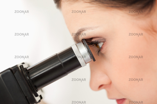 Dark-haired scientist looking through a microscope