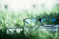 Studying outdoors: Glasses on book outdoors in the park, spring time