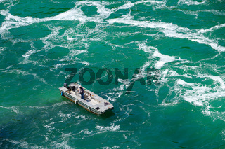 Fisher on boat in river with strong current. Copy space.
