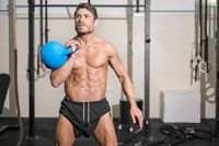 Muscular athletic bodybuilder fitness model posing after exercises in gym.