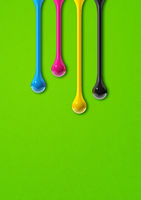 cmyk ink drops on green paper background