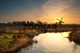 windmill during sunrise reflected in river