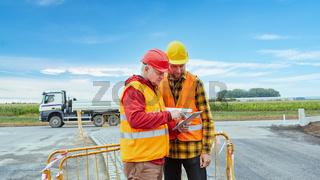 Zwei Bauarbeiter auf Baustelle mit Tablet Computer