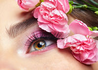 Closeup portrait of female eye with pink beauty makeup and carnation flowers .