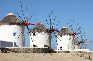 Windmills on a hillside near the sea in Mykonos Island