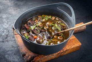 Modern style traditional French boeuf bourguignon with mushrooms and carrots in red wine sauce served as close-up in a Design casserole