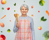 smiling senior woman in apron with wooden spoons