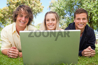 Close-up of three happy students in a park
