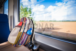 Backpack on the train near the window. Travel conceptual image.