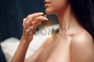 A young girl holds a pipette with cosmetic oil. Skin care concept