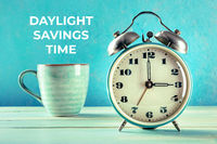 Daylight Saving Time concept. A retro alarm clock with a cup of coffee