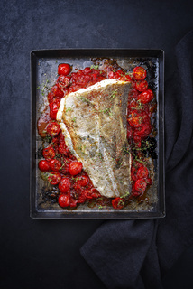Traditional skinned backed skrei cod fish filet with tomato salsa ragu and herbs served as top view on a rustic metal sheet with copy space